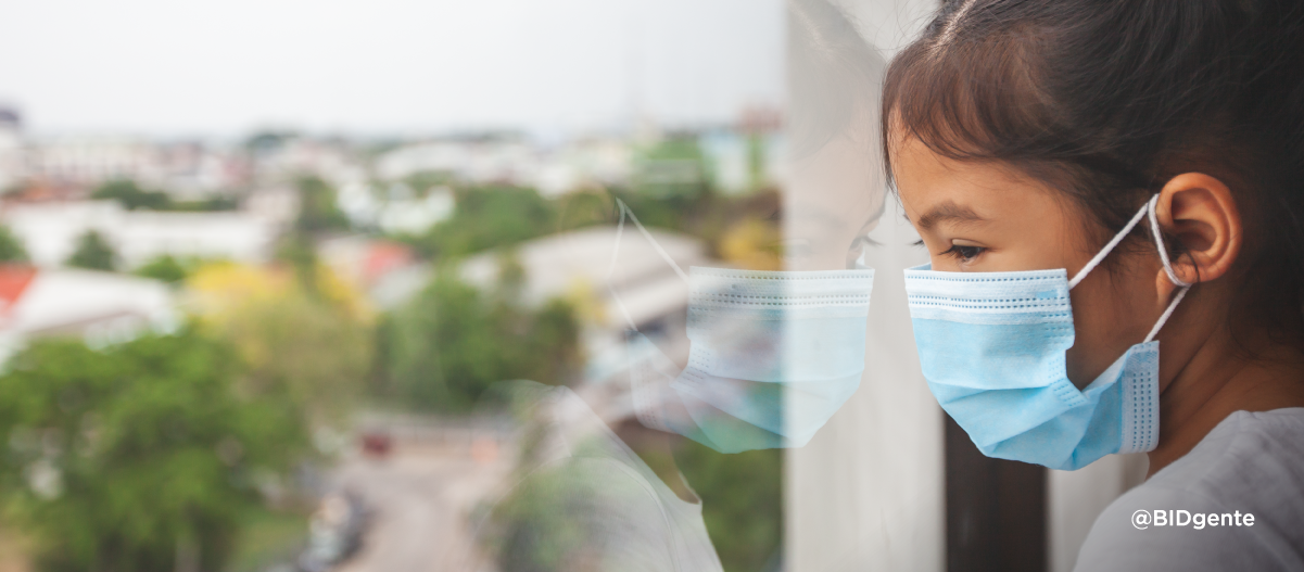 Niño con mascarilla protectora mira por la ventana de su casa