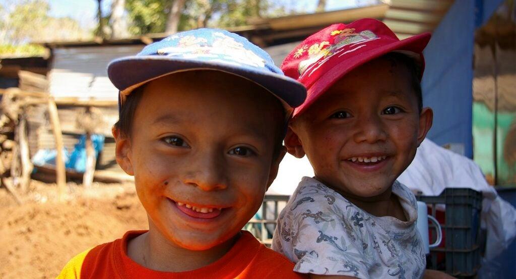 niño de 3 años y niño de 6 años mirando a la cámara sonrientes