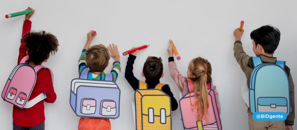 5 niños de 6 años con sus mochilas escriben en una pizarra