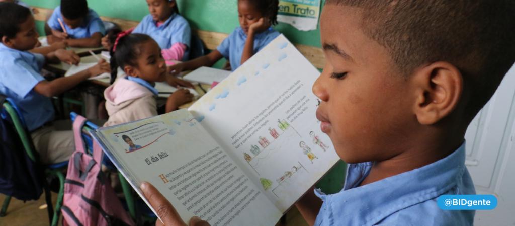 niño 6 años lee un libro frente a sus compañeros