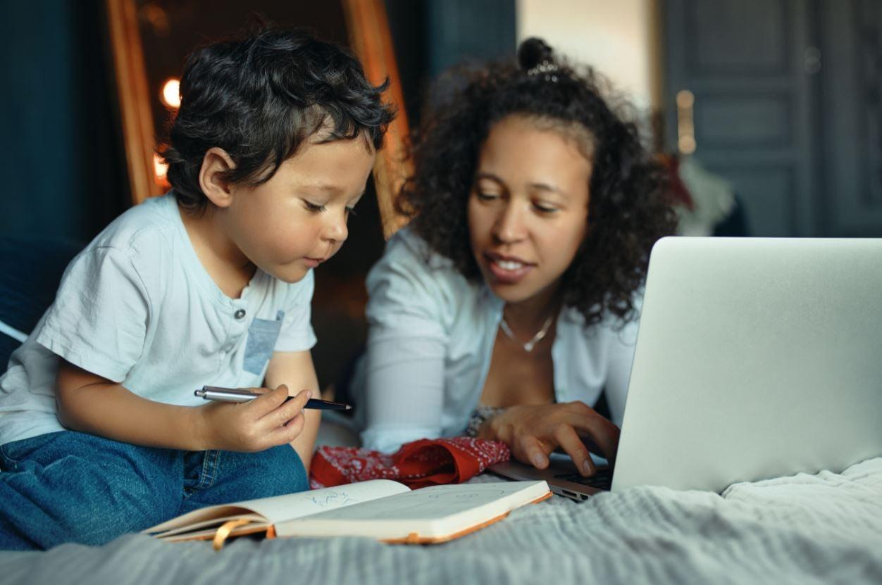 madre y su hijo de 3 años ven juntos un libro y una computadora