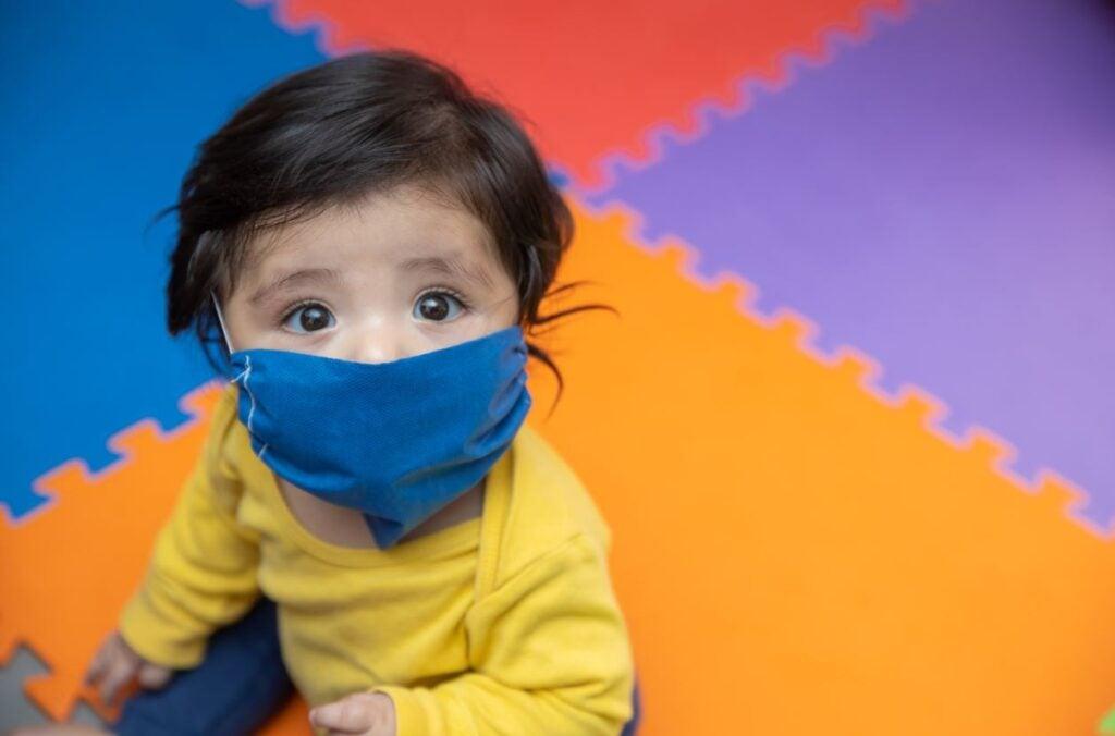 Niño de un año usando una mascarilla en jardín de infantes