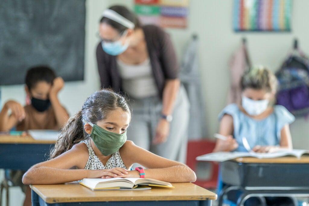 Niña usando una máscara atendiendo una clase