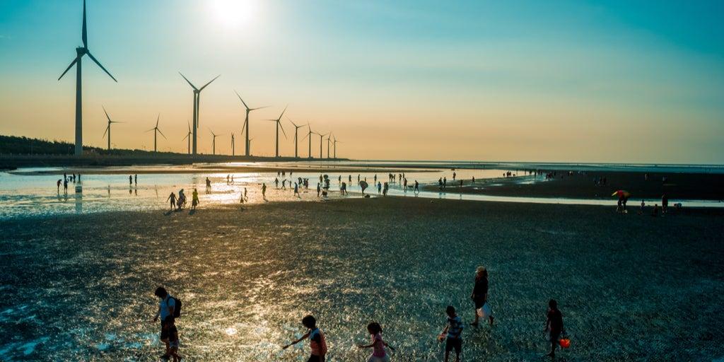 Turbinas eólicas en el mar sobre puesta del sol- personas caminando