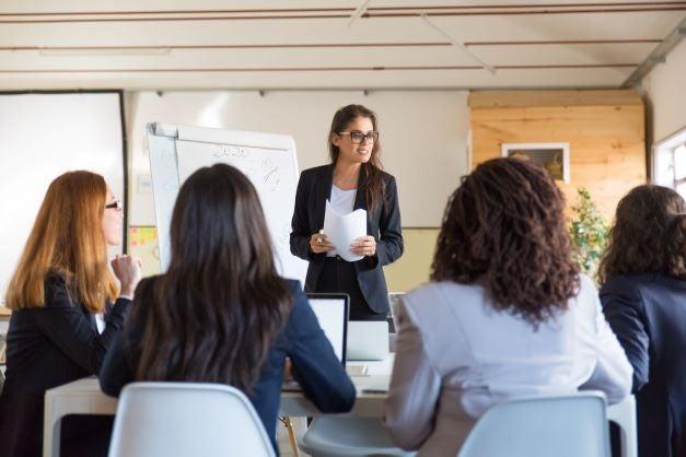 Mujer hablando con mesa de empresarias