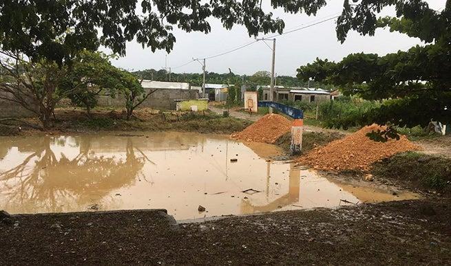"""La cancha de baloncesto junto a la escuela, conocida en La Ciénaga como la """"laguna de la malaria""""."""