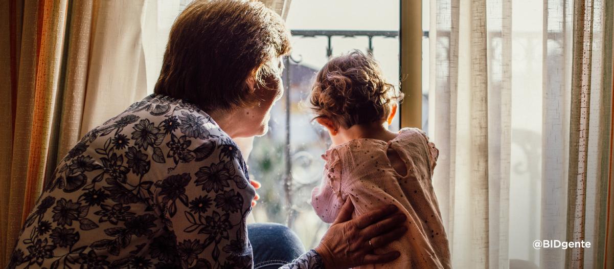 una abuela y su nieta miran por la ventana