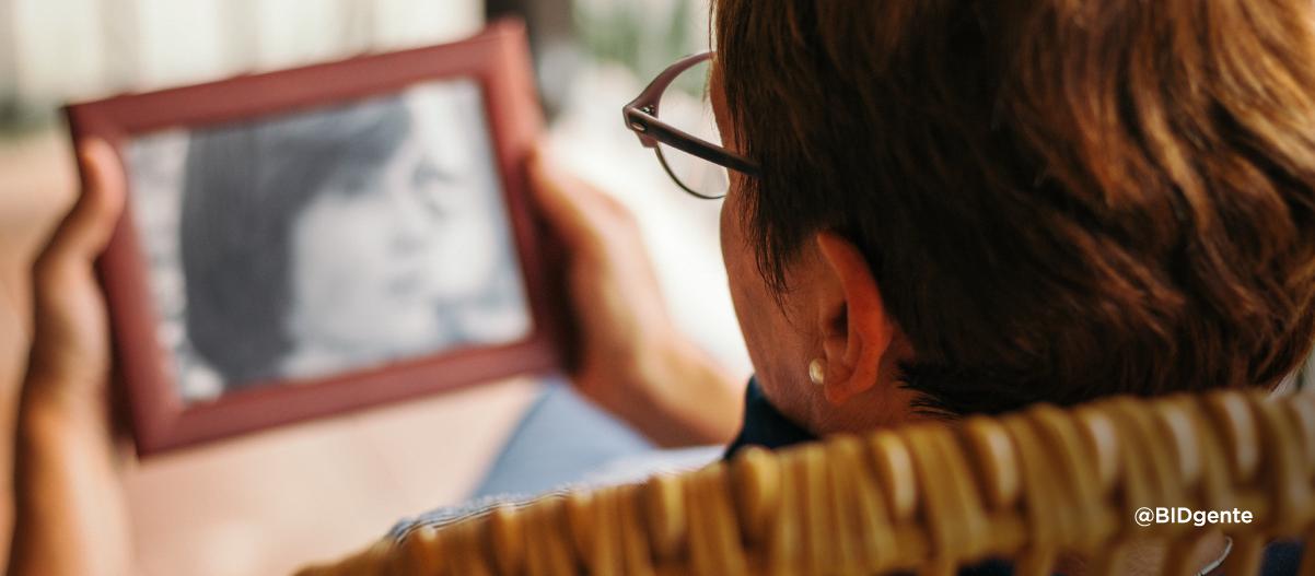 Una mujer adulta mayor con demencia mira una foto en blanco y negro