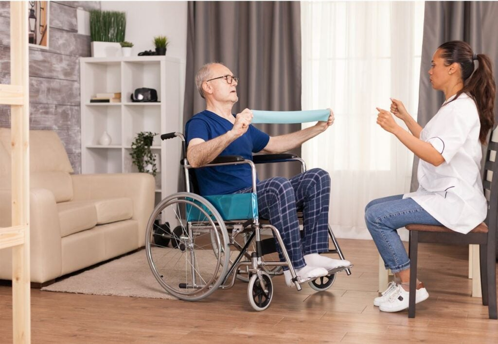 Una persona mayor hace ejercicio con una cuidadora